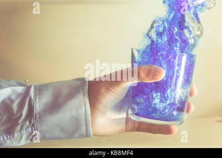 A hand is holding a glass containing blue liquid which is coming out - Stock Photo