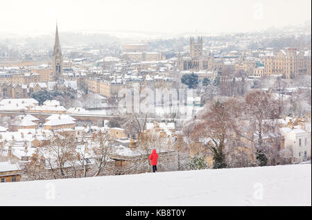 Person in a red jacket looking at the City of Bath from a snow covered hill. - Stock Photo