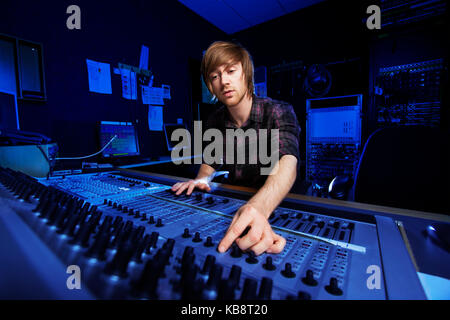 Man using a sound mixing desk in a recording studio - Stock Photo