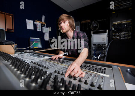 Man using a sound mixing desk in a recording studio. - Stock Photo