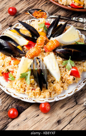 Traditional vegetable paella with seafood on wooden background - Stock Photo