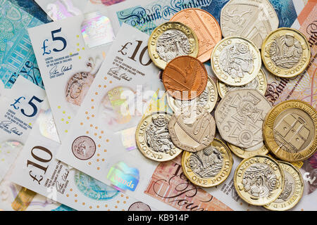 British UK money sterling £10 and £5 notes GBP and a pile of new issue pounds one pound coins cash. Saving money - Stock Photo