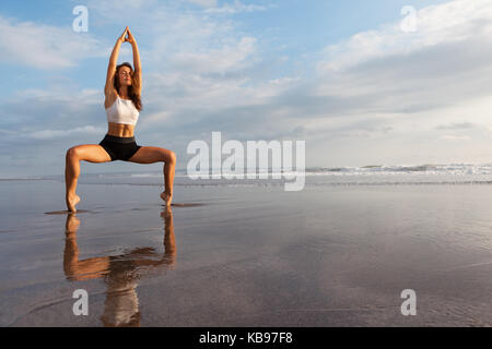 Meditation on sunset sky background. Young active woman in yoga pose on sea beach, stretching to keep fit, health. - Stock Photo