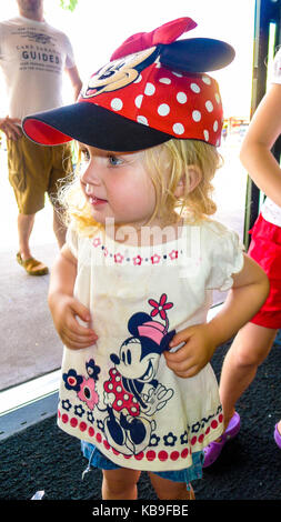 Toddler wearing a minnie mouse t-shirt and hat with ears in red and white polka dot in Disney World, Florida, USA - Stock Photo