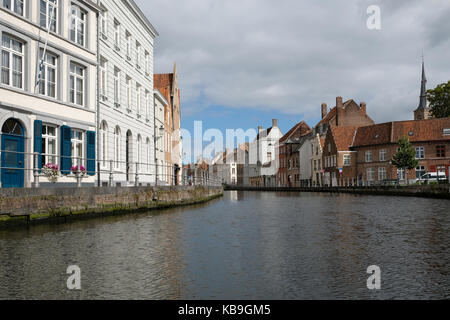 Typical canal scene in Bruges / Brugge, Belgium showing medieval buildings overlooking the water - Stock Photo