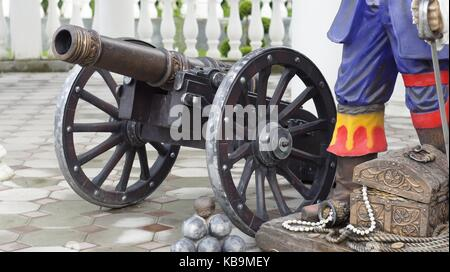 A copy of an old cannon with cores in the style of the times of colonization of the New World and the era of pirates, - Stock Photo