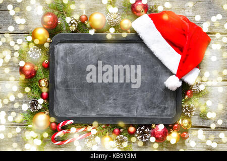 Classic christmas and new year composition chalk board, balls, toys, candy, fir branches on vintage wooden background - Stock Photo