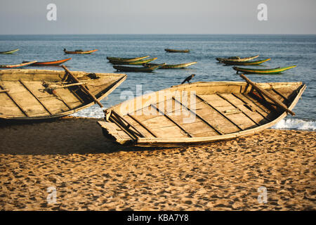Sunset casts its soft golden light on traditional Indian fishing boats moored on the beach while others float in - Stock Photo