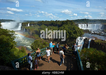 Tourists on viewing platform on Brazil side of Iguazu Falls, looking at Argentinian  side, South America - Stock Photo