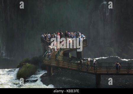 Tourists on viewing platform on Brazil side of Iguazu Falls, Brazil - Argentina border, South America - Stock Photo