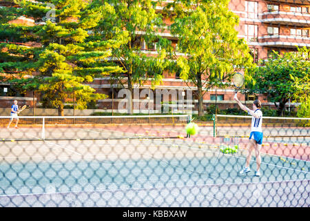 Washington DC, USA - August 4, 2017: Tennis players couple, man, woman playing, serving in Francis Stevens Playground - Stock Photo