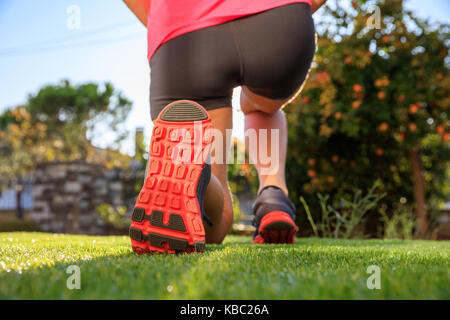 Female runner feet on the grass at sunrise or sunset, closeup on shoes - Stock Photo