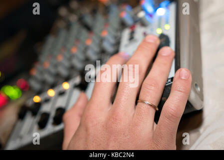 DJ working on a audiomixer at a nightclub. Close-up of hands adjusting quality of music using a knobs of the audio - Stock Photo