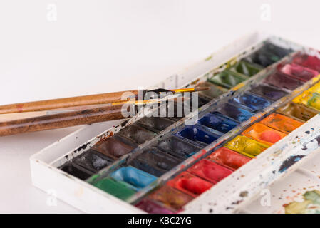 Image of colorful paint buckets and brushes isolated over white background - Stock Photo