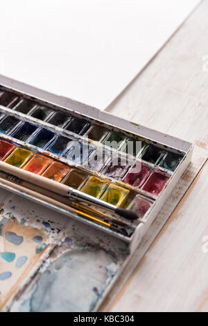 Image of colorful paint buckets and brushes isolated over white and wooden background - Stock Photo