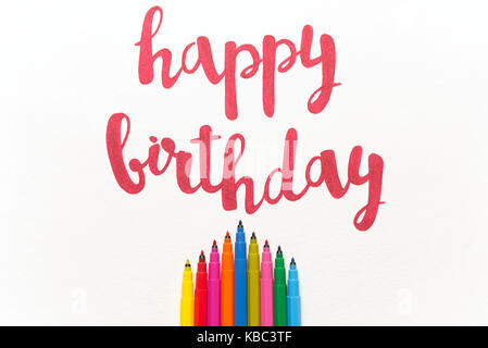 Inspirational phrase 'Happy birthday' for greeting cards and posters drawing with red marker on white paper. Top - Stock Photo