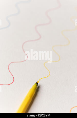 Close up of yellow highlighter painting wavy line on white paper. Lines for logo, text - Stock Photo