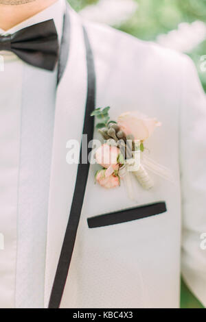 Close-up view of the little boutonniere of pink roses on the groom`s suit jacket. - Stock Photo