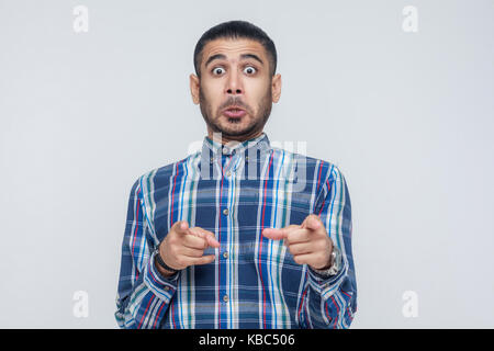 The seriosly man, wearing blue shirt, opening mouths widely, having surprised shocked looks, pointing finger at - Stock Photo