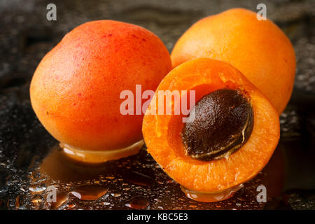Close up of two whole and one half sliced apricot fruits with the stone, ripe, freshly washed with water drops on - Stock Photo