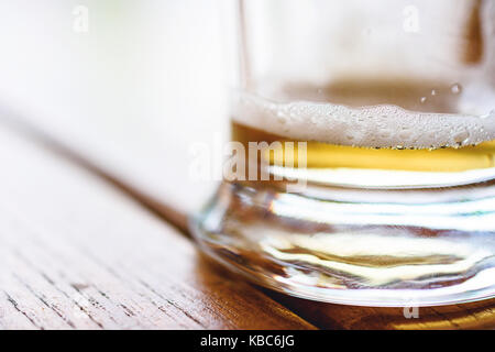 Close-Up Of Partially Finished Cold Glass Of Beer With Frothy Foam And Bubbles On Rough Wooden Table - Stock Photo