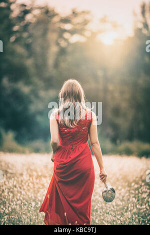 girl walking in a field at sunset, in a red dress, holdinh a silver mirror - Stock Photo