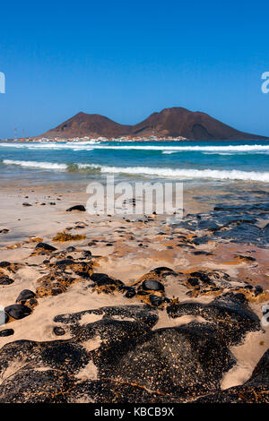 Volcanic basalt rocks on the beach at the Atlantic Ocean. Calhau town, extinct volcano crater in Cape Verde, Sao - Stock Photo