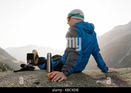 Alpinist enjoys the sunrise in the Swiss Alps during a break and prepares a hot tea - Stock Photo