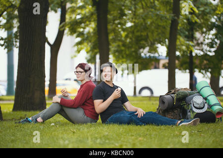 Teenagers tourists with backpacks are eating the icecream in the park - Stock Photo