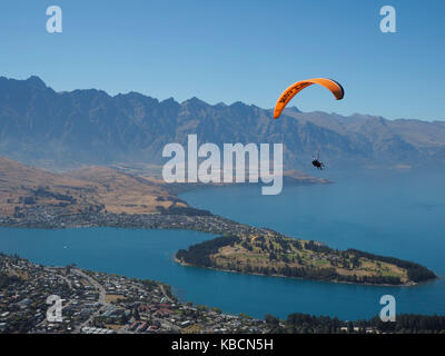 Paragliders soaring above Lake Wakatipu in Queenstown, New Zealand - Stock Photo