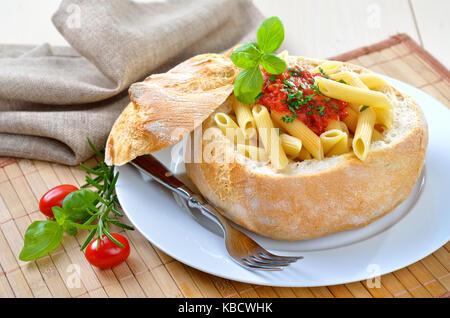 Pasta with tomato sauce filled in Italian ciabatta bread - Stock Photo