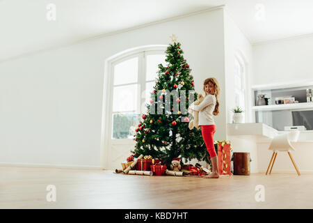 Girl holding teddy bear standing near Christmas tree. Gifts placed around decorated Christmas tree at home. - Stock Photo