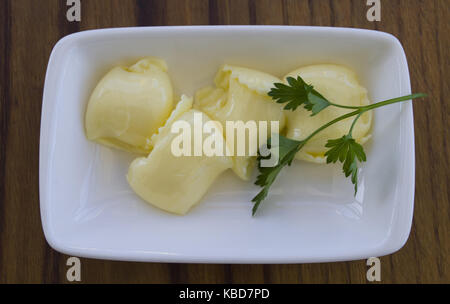 pat of fresh farm butter on a butter dish - Stock Photo