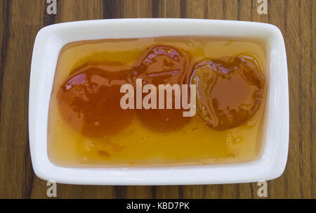 apricot jam in a glass bowl fresh apricots in a basket on a wooden background - Stock Photo