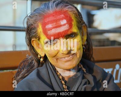 Middle-aged Shaivite female sadhu (holy woman aka sādhvī who worships Shiva) with very distinctive tripundra on - Stock Photo