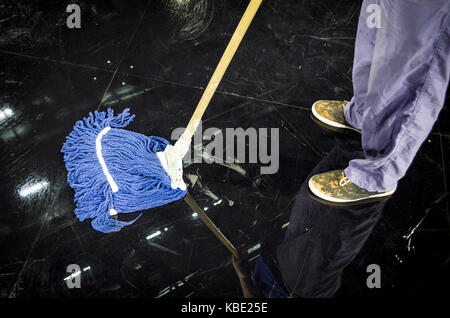 young man with mop cleaning floor in the room closeup - Stock Photo