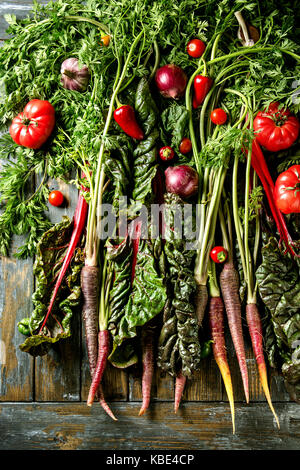 Raw organic purple carrot with variety of vegetables tomatoes, pepper, chard, garlic, onion on haulm over old wooden - Stock Photo