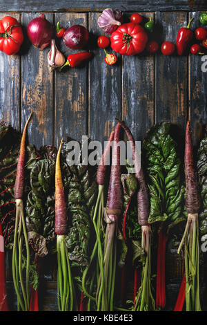 Raw organic purple carrot with chard leaves and variety of vegetables tomatoes, pepper, garlic, onion over old wooden - Stock Photo
