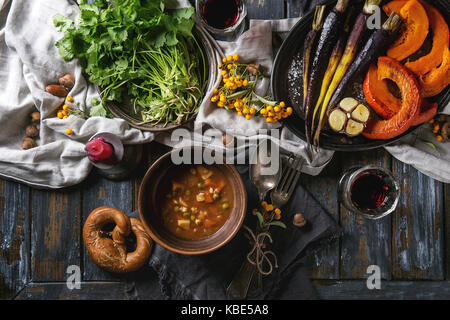 Holiday table decoration setting with bowls of hot soup, baking pumpkin, carrot, garlic, fresh coriander, pretzels - Stock Photo