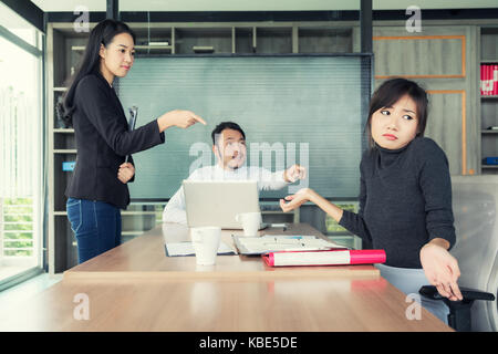 Group of Asian business people looking at businesswoman and blaming colleague for failure, bad work results in business - Stock Photo