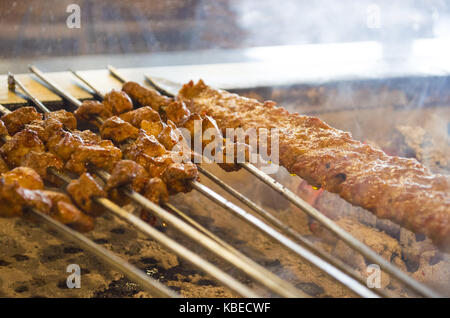 turkish style kebab cooking adana kebabs on the restaurant style grill smoke coming out from them