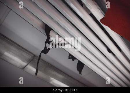 Low Angle View Of Black Backpack Braces Falling Through Luggage Rack In Train - Stock Photo