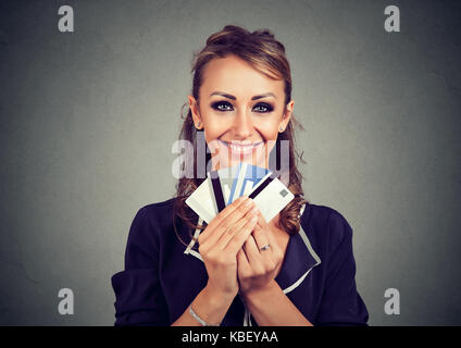 Woman with many different credit loyalty discount cards isolated on gray wall background. - Stock Photo