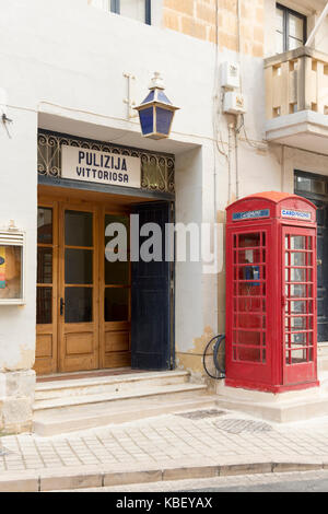 The police station in Vittoiosa Malta with an old UK red telephone box outside in the street - Stock Photo