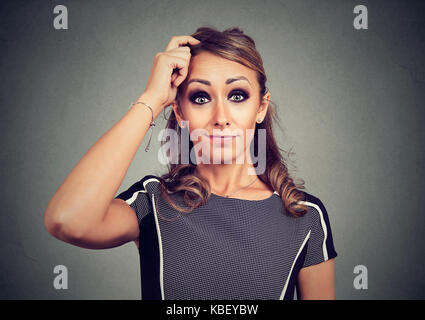 Portrait of confused funny looking woman scratching head - Stock Photo