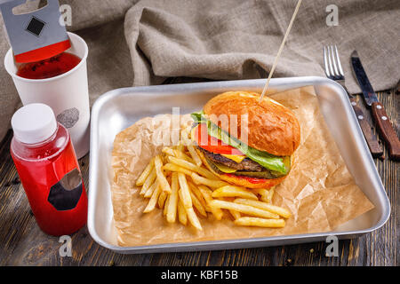 Big hamburger with three beef cutlet and vegetables with golden crispy french fries and toasted crispy toast on - Stock Photo