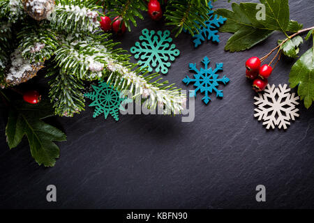 Background christmas decoration twig, red berries and wooden stars on back slate. - Stock Photo