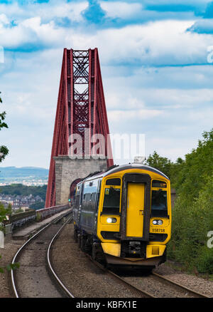 View of Scotrail passenger train approaching Dalmeny Station after crossing Forth Railway Bridge in Lothian , Scotland, - Stock Photo
