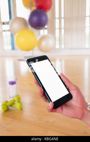 Womans hand holding mobile phone in the gym - Stock Photo