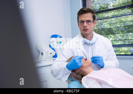 Portrait of dentist cleaning woman teeth while standing against wall at dental clinic - Stock Photo